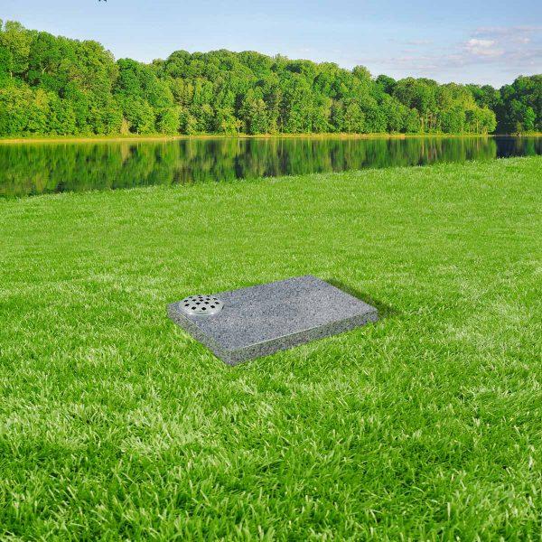 Light grey granite tablet memorial mounted on grass